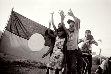 kids dancing in front of an aboriginal flag